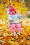 Μικρό κορίτσι στην ταλάντευση στο πάρκο φθινοπώρου στοκ εικόνα
