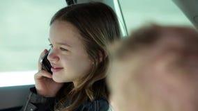Μικρό κορίτσι στη πίσω θέση του αυτοκινήτου που κάνει μια κλήση με το τηλέφωνο φιλμ μικρού μήκους