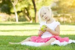 Μικρό κορίτσι στη χλόη που τρώει την υγιή Apple Στοκ εικόνες με δικαίωμα ελεύθερης χρήσης
