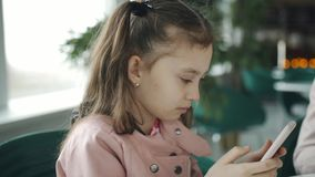 Μικρό κορίτσι στις φωτογραφίες μιας καφέδων προσοχής στο smartphone σε ανα απόθεμα βίντεο