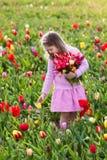 Μικρό κορίτσι στον κήπο λουλουδιών τουλιπών Στοκ Φωτογραφία