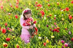 Μικρό κορίτσι στον κήπο λουλουδιών τουλιπών Στοκ φωτογραφία με δικαίωμα ελεύθερης χρήσης