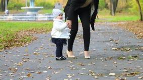 Μικρό κορίτσι στον περίπατο φουστών και μητέρων στο πάρκο φθινοπώρου απόθεμα βίντεο
