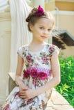 Μικρό κορίτσι στο ζωηρόχρωμα φόρεμα και τα λουλούδια Στοκ Φωτογραφία