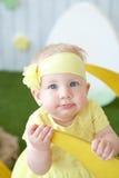 Μικρό κορίτσι στο κίτρινο φόρεμα με τη διακόσμηση στη συνεδρίαση τρίχας της Στοκ εικόνα με δικαίωμα ελεύθερης χρήσης