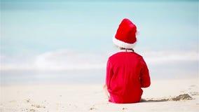 Μικρό κορίτσι στο καπέλο Χριστουγέννων στην άσπρη παραλία κατά τη διάρκεια των διακοπών Χριστουγέννων φιλμ μικρού μήκους