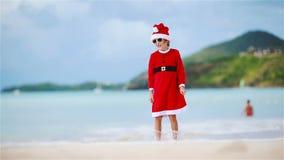Μικρό κορίτσι στο καπέλο Χριστουγέννων στην άσπρη παραλία κατά τη διάρκεια των διακοπών Χριστουγέννων απόθεμα βίντεο