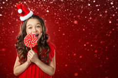 Μικρό κορίτσι στο καπέλο santa με την καραμέλα στο κόκκινο υπόβαθρο στενός κόκκινος χρόνος Χριστουγέννων ανασκόπησης επάνω Στοκ εικόνα με δικαίωμα ελεύθερης χρήσης