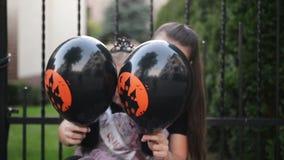 Μικρό κορίτσι στο κοστούμι πριγκηπισσών που κρατά ένα μαύρο μπαλόνι Φαίνεται πολύ ευτυχής επειδή σήμερα είναι διακοπές αποκριών απόθεμα βίντεο