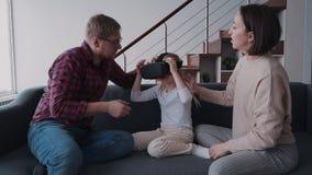 Μικρό κορίτσι στο κράνος vr ή γυαλιά που κάθονται κοντά στο γονέα της απόθεμα βίντεο