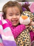 Μικρό κορίτσι στο κρεβάτι με το παιχνίδι στοκ φωτογραφία