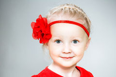 Μικρό κορίτσι στο κόκκινο φόρεμα με το κόκκινο λουλούδι στοκ φωτογραφίες