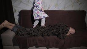 Μικρό κορίτσι στο μπουρνούζι που ξυπνά τον πατέρα της Ύπνοι ατόμων στον καναπέ απόθεμα βίντεο