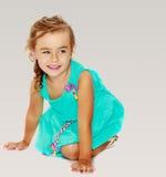 Μικρό κορίτσι στο μπλε φόρεμα στα γόνατά της Στοκ Εικόνες