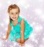 Μικρό κορίτσι στο μπλε φόρεμα στα γόνατά της Στοκ φωτογραφία με δικαίωμα ελεύθερης χρήσης