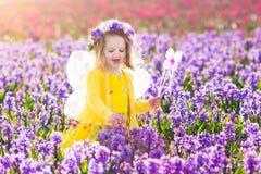 Μικρό κορίτσι στο παιχνίδι κοστουμιών νεράιδων στον τομέα λουλουδιών Στοκ εικόνες με δικαίωμα ελεύθερης χρήσης
