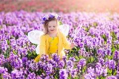 Μικρό κορίτσι στο παιχνίδι κοστουμιών νεράιδων στον τομέα λουλουδιών Στοκ Εικόνα