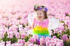 Μικρό κορίτσι στο παιχνίδι κοστουμιών νεράιδων στον τομέα λουλουδιών Στοκ Φωτογραφία