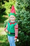 Μικρό κορίτσι στο πουλόβερ νεραιδών και καπέλο που περιμένει Χριστούγεννα στο ξύλο Στοκ φωτογραφίες με δικαίωμα ελεύθερης χρήσης