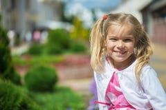 Μικρό κορίτσι στο πράσινο πάρκο θερινών πόλεων στοκ φωτογραφία