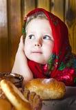 Μικρό κορίτσι στο ρωσικό σάλι με τους ρόλους και το μέλι Στοκ Φωτογραφία