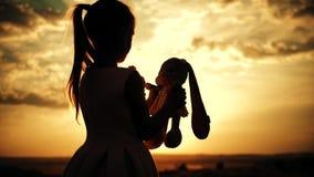 Μικρό κορίτσι στο ρόδινο εορταστικό φόρεμα που κρατά το μεγάλο παιχνίδι λαγουδάκι βελούδου στο ηλιοβασίλεμα Σκιαγραφία ενός παιδι απόθεμα βίντεο