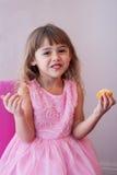 Μικρό κορίτσι στο ρόδινο φανταχτερό φόρεμα, που τρώει το γλυκό cupcake Στοκ φωτογραφία με δικαίωμα ελεύθερης χρήσης