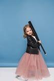 Μικρό κορίτσι στο σακάκι δέρματος και το ρόδινο ρόπαλο του μπέιζμπολ εκμετάλλευσης φουστών και το χαμόγελο στη κάμερα Στοκ Φωτογραφία