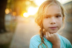 Μικρό κορίτσι στο υπόβαθρο του ηλιοβασιλέματος στην οδό Στοκ Εικόνες