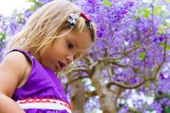 Μικρό κορίτσι στο υπόβαθρο του πορφυρού ξύλου Στοκ Εικόνες