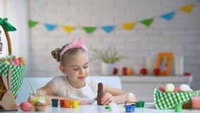 Μικρό κορίτσι χαριτωμένο headband που χαμογελά και που θέτει στη κάμερα με το λαγουδάκι σοκολάτας απόθεμα βίντεο