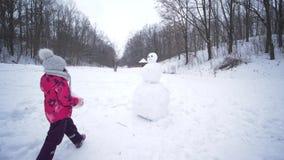 Μικρό κορίτσι sculpts ένας χιονάνθρωπος στο χιόνι κατά τη διάρκεια χιονοπτώσεων στις χειμερινές διακοπές φιλμ μικρού μήκους