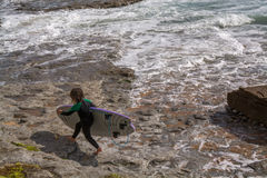 Μικρό κορίτσι surfer Ribeira de Ilhas Beach σε Ericeira Πορτογαλία Στοκ Εικόνες