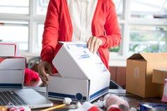 Μικρό κουτί από χαρτόνι συσκευασίας ιδιοκτητών επιχείρησης ξεκινήματος στον εργασιακό χώρο Στοκ Εικόνα