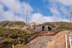 Μικρό κτήριο στο λόφο με την ξύλινη σκάλα που οδηγεί σε το μπλε αυξομειούμενος ο&u στοκ φωτογραφία