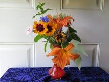 Μικρό κόκκινο βάζο Wildflowers γυαλιού & κίτρινη πρασινάδα Daylilies Στοκ εικόνες με δικαίωμα ελεύθερης χρήσης