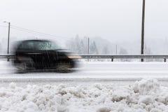 Μικρό μαύρο αυτοκίνητο στη θαμπάδα κινήσεων στο δρόμο στο χειμερινό τοπίο, με το χιονώδη καιρό στοκ εικόνες
