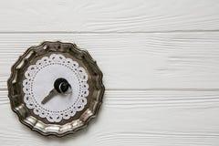 Μικρό μαύρο κλειδί σε ένα πιάτο χάλυβα Άσπρα ξύλινα υπόβαθρο και διάστημα για το κείμενο Στοκ φωτογραφίες με δικαίωμα ελεύθερης χρήσης