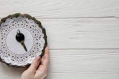 Μικρό μαύρο κλειδί σε ένα πιάτο χάλυβα Άσπρα ξύλινα υπόβαθρο και διάστημα για το κείμενο Στοκ φωτογραφία με δικαίωμα ελεύθερης χρήσης