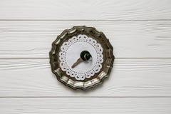Μικρό μαύρο κλειδί σε ένα πιάτο χάλυβα Άσπρα ξύλινα υπόβαθρο και διάστημα για το κείμενο Στοκ Εικόνες