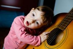 Μικρό μικρό παιδί που ακούει τον ήχο μιας κιθάρας στοκ φωτογραφία με δικαίωμα ελεύθερης χρήσης