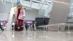 Μικρό ξανθό κορίτσι σε ένα ρόδινο χειμερινό παλτό με την κόκκινη βαλίτσα που περπατά πέρα από την αίθουσα αναμονής στον αερολιμέν απόθεμα βίντεο