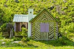 Μικρό ξύλινο εξοχικό σπίτι κάτω από το λόφο στα ξύλα Στοκ φωτογραφία με δικαίωμα ελεύθερης χρήσης