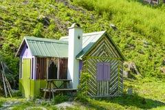 Μικρό ξύλινο εξοχικό σπίτι κάτω από το λόφο στα ξύλα Στοκ Εικόνα