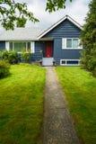 Μικρό οικογενειακό σπίτι με τον πράσινο χορτοτάπητα και διακοσμητικά λουλούδια στην πόρτα στοκ εικόνα με δικαίωμα ελεύθερης χρήσης