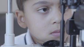 Μικρό παιδί αφροαμερικάνων που κάνει τη δοκιμή με optometrist στο ιατρικό γραφείο κοντά επάνω Ιατρικός, υγεία, οφθαλμολογία απόθεμα βίντεο