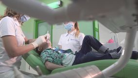 Μικρό παιδί δύο οικογενειακών θεραπευθε'ν οδοντίατρος δοντιών Βρισκόταν στην οδοντική καρέκλα και χαμογελά φιλμ μικρού μήκους