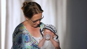 Μικρό παιδί, κοριτσάκι, παιδί, πόσιμο νερό μωρών από το μπουκάλι καθμένος στα γόνατα της γιαγιάς απόθεμα βίντεο