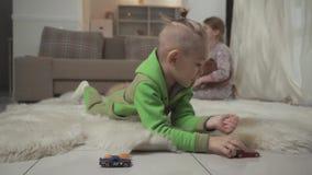 Μικρό παιδί με τα μοντέρνα παιχνίδια κουρέματος με τα toycars του που βρίσκονται στο πάτωμα στο χνουδωτό τάπητα Παιχνίδι αδελφών  απόθεμα βίντεο