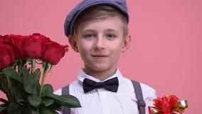 Μικρό παιδί με την ανθοδέσμη των τριαντάφυλλων και του κιβωτίου δώρων έτοιμου για την ημερομηνία, ημέρα βαλεντίνων απόθεμα βίντεο